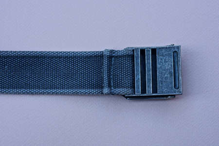 a belt made of fabric with a gray metal buckle lies on a pink table 免版税图像