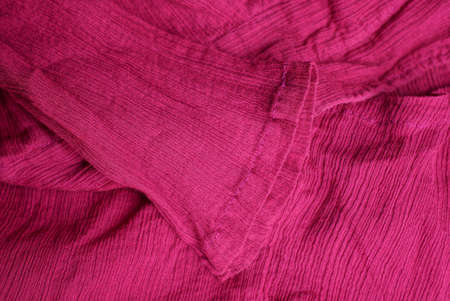 red fabric texture from a piece of crumpled clothing with a sleeve