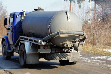 one big truck with a gray barrel and a hose goes on an asphalt road