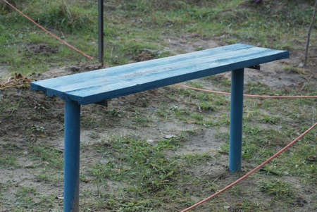 one empty blue wooden bench stands on gray ground and in green grass outside Stockfoto - 163373895