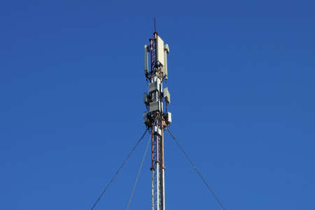 high iron pole with gray antennas on the street against a blue sky Stockfoto