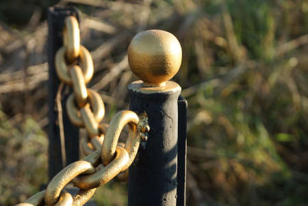 part of a decorative fence made of a black iron pillar and a yellow chain in green grass outside