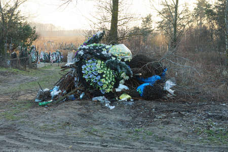 a large pile of garbage from colored wreaths and flowers on the ground in the street in the cemetery