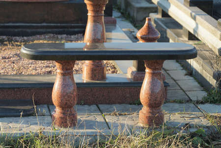 one empty black brown marble bench stands outside in the cemetery