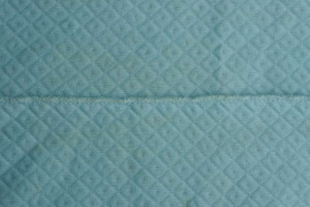 Blue fabric background of a fragment of crumpled cloth and seam
