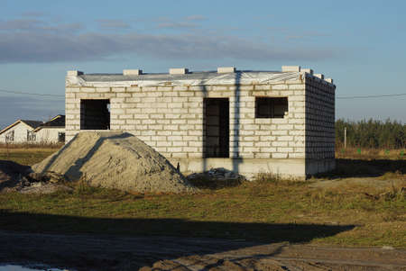 one white private unfinished brick house on a construction site in green grass with a pile of gray sand against a blue sky