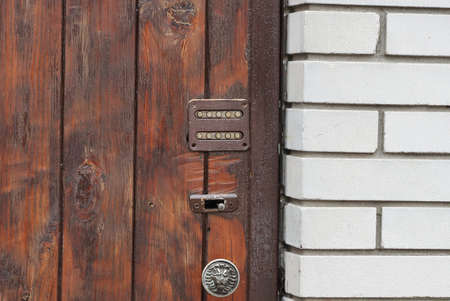 combination lock and doorknob on brown boards of a closed door against a white brick wall in the street