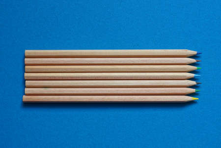set of long brown wooden pencils lie on a blue table Stockfoto