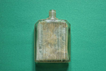 one old gray dirty glass bottle for perfume lies on a green table