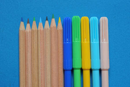 set of brown wooden pencils and colored plastic markers on blue background