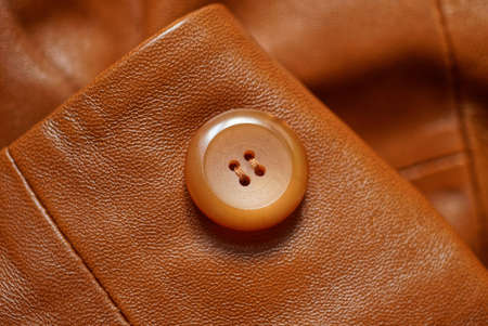 one big plastic round button on a leather brown jacket