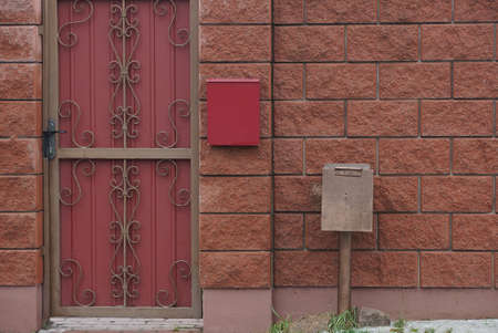 one red metal door with a wrought iron pattern and part of a brown fence wall with a mailbox and a box for electrical wires Stockfoto