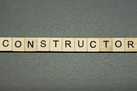 text the word constructor from brown wooden small letters with black font on an gray table