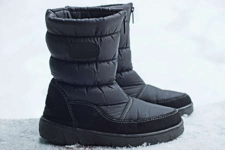 two black boots of matter standing on white snow on the street Stockfoto