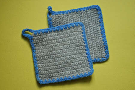 two gray knitted square napkins made of woolen fabric lie on a yellow table Stockfoto