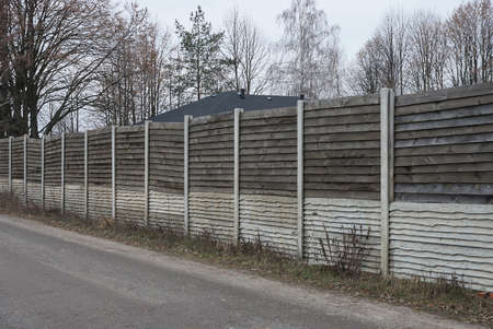 long gray white wall of wooden private fence wall on street by a Stockfoto