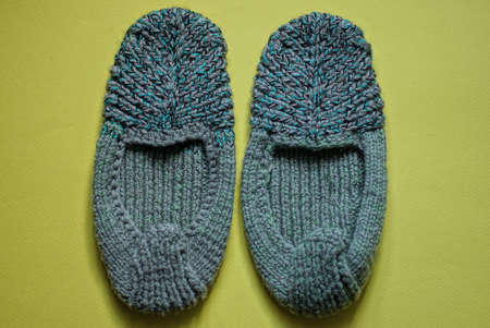 two gray green knitted woolen slippers stand on a yellow table Stockfoto - 163365068