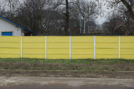 long private concrete yellow fence on a rural street in the green grass Stockfoto