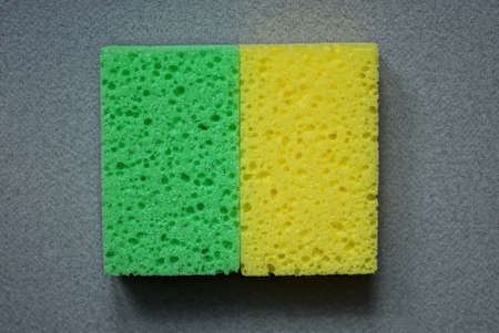 two yellow and green foam sponges lie on a gray table Stockfoto