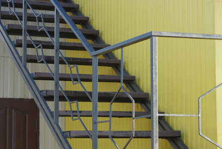 part of a large staircase with gray steps with metal handrails with a pattern against the yellow wall outside