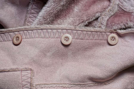 three plastic buttons on a brown suede winter jacket with fur