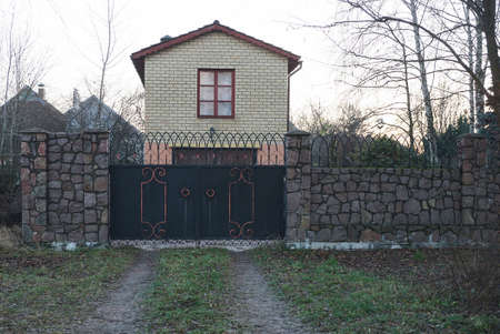 closed black iron gate on a gray stone wall of a fence in green grass in front of a private brick house with a window