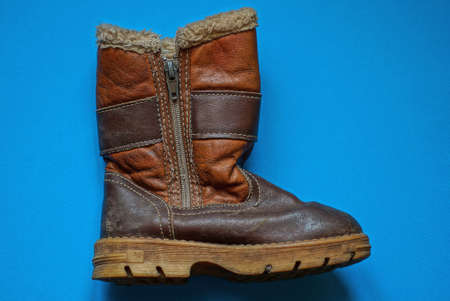 one old brown leather boot with zip and fur lies on a blue table Stockfoto