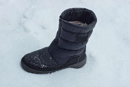one black boot of matter standing on white snow on the street Stockfoto