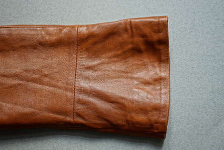 one brown leather sleeve of a jacket lies on a gray table