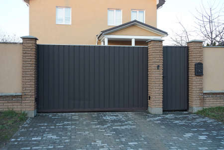 a large iron brown gate and a closed door with a part of a fence outside on a gray sidewalk