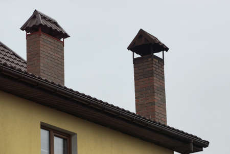 two brown brick chimneys on the roof of a private house against a gray sky Stockfoto