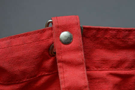 gray metal rivet and carabiner in a red cloth harness on an old bag Stockfoto