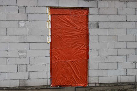 white brick wall of an unfinished house with a door closed with red plastic cellophane on the street Stockfoto