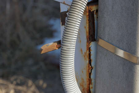 gray plastic hose on a concrete pole outside