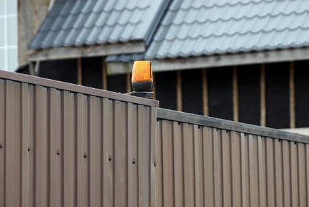 one red signal lamp on the brown metal wall of the fence at the closed gate