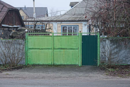 one closed old green iron gate and gray fence on rural street Stockfoto - 163357034
