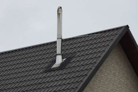 one long chimney from a white metal pipe on a brown tiled roof of a private house against a gray sky