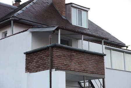 one open brown brick balcony on the white wall of the attic of a private house under a tiled roof against the sky
