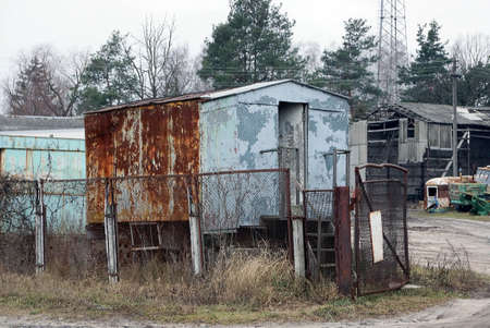 one old gray metal trailer booth in brown rust with an open door stands on the street behind a fence made of iron mesh