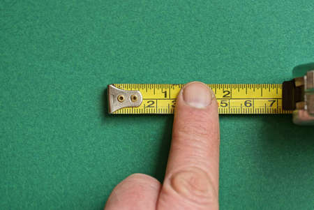 finger holds a yellow metal ruler on a construction tape measure on a green table
