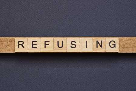 text on word refusing from gray wooden letters on a black background