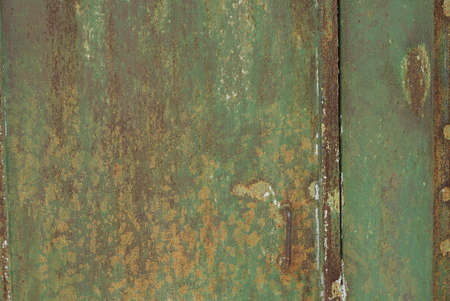 green metal texture from an old iron wall with a brown rusty seam