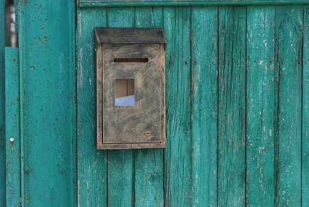 one brown gray metal mailbox hanging on a green wooden fence in the street