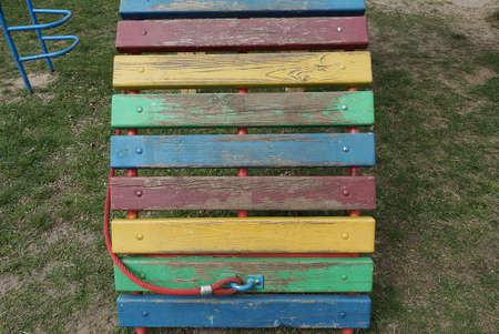 part of a colored bench made of wooden planks stands in the green grass on the street Standard-Bild