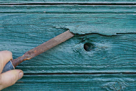 hand holds brown old rusty iron chisel in green wood plank wall Standard-Bild
