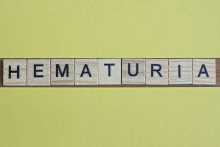 word hematuria made from wooden letters lies on a yellow table Standard-Bild