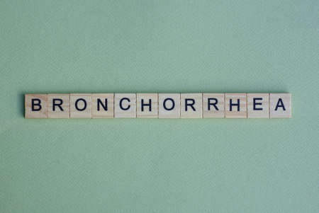 gray word bronchorrhea from small wooden letters on a green table