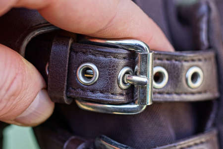 fingers on his hand hold a brown harness belt with a gray metal buckle on the bag Standard-Bild
