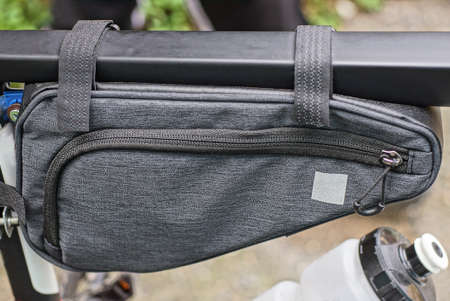 one gray closed fabric glove compartment hangs on a black metal bicycle frame outside