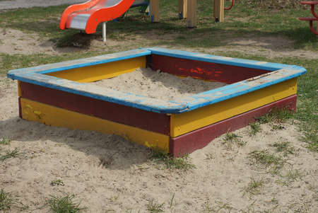 one big colored square wooden sandbox with white sand stands on the ground and green grass in the playground
